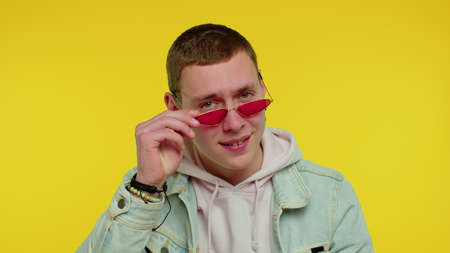 Portrait of seductive cheerful teen stylish boy in denim jacket wearing sunglasses, charming smile. People emotions concept. Young lovely adult man posing isolated on yellow studio wall background 版權商用圖片
