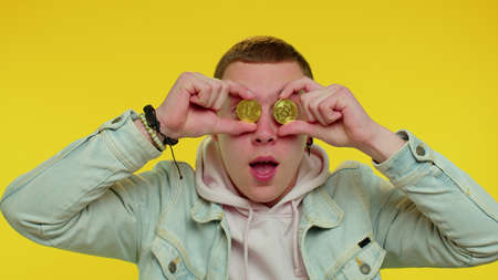 Handsome rich stylish teen boy showing golden bitcoins. Achievement career wealth, cryptocurrency investment, mining, future technology. Young adult cute man fooling, making faces. Happy businessman 版權商用圖片
