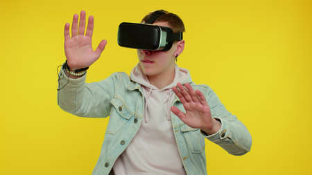 Teen stylish boy using virtual reality futuristic technology VR app headset helmet to play simulation 3D 360 video game, drawing. Young man on yellow studio background. People sincere emotions
