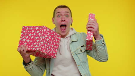 Cheerful teen stylish young man opening gift box, unwrapping birthday surprise and expressing great happiness amazement, satisfied with best present bonus. Adult boy on yellow studio wall background 版權商用圖片