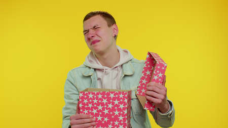 Handsome stylish teen boy unwrapping gift and expressing disappointment, dislike to bad present, guy dissatisfied with birthday surprise. Young adult man indoor isolated on yellow studio background 版權商用圖片