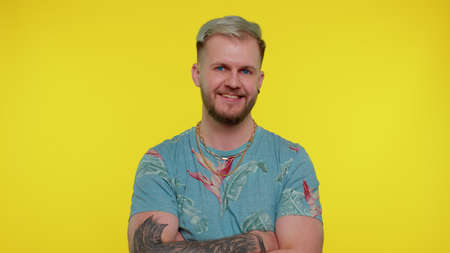 Cheerful lovely bearded adult man in fashionable t-shirt smiling and looking at camera. Young fashion model guy boy with blue eyes indoors studio shot isolated on yellow background. Male nature beauty