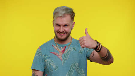 Bearded adult man in fashionable t-shirt raises thumbs up agrees with something or gives positive reply recommends advertisement likes good. Young fashionable guy isolated on yellow studio background 版權商用圖片