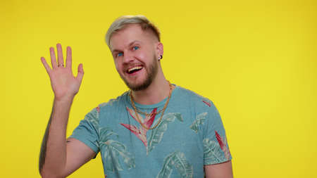 Handsome bearded guy smiling friendly at camera and waving hands gesturing hello or goodbye, welcoming with hospitable expression. Young fashionable man indoors isolated on yellow wall background