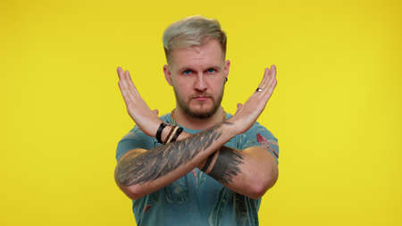 No stop. Stylish adult guy say no, hold palm folded crossed hands in stop danger gesture, warning of finish, prohibited access, declining communication, body language. Young man on yellow background