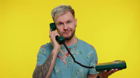 Hey you, call me back. Cheerful tourist man secretary in blue t-shirt talking on wired vintage telephone of 80s, says hey you call me back. Young guy posing isolated on yellow studio wall background