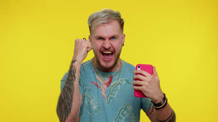 Happy excited joyful stylish tourist man in t-shirt use mobile cell phone typing browsing say wow yes found out great big win news doing winner gesture. Young adult guy on yellow studio background
