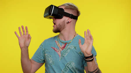 Amazed tourist adult man using headset helmet app to play simulation game. Watching virtual reality 3D 360 video. Young guy in VR goggles isolated on yellow background. Addiction from new technology