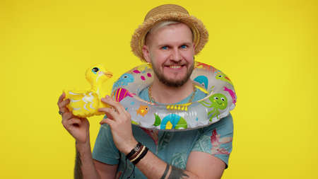 Traveler tourist bearded adult man dancing fooling with swimming ring and inflatable duck toy, travel on weekends. Concept summer vacation, journey, trip to seaside. Young guy boy dancing, celebrating 版權商用圖片