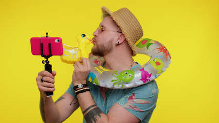 Handsome bearded adult man traveler blogger in sunglasses, taking selfie on mobile phone, communicating video call online with family, making vlog. Young fashionable guy on yellow studio background