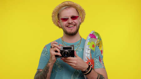 Bearded stylish man tourist in fashion t-shirt. Photographer taking photos on retro camera and smiling. Young guy on yellow studio background. People sincere emotions. Travel, summer holiday vacation