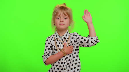 I swear to be honest. Responsible sincere little kid child in shirt raising hand to take oath, promising to be honest and to tell truth keeping hand on chest on chroma key wall. Children girl emotions
