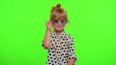 Playful happy little blonde stylish teen kid child girl in sunglasses blinking eye, looking at camera with smile, winking and flirting, expressing optimism. Young children on chroma key background
