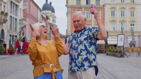 Senior old stylish tourists man and woman looking smartphone display sincerely rejoicing win, receiving message with good news, success luck. Elderly grandmother, grandfather enjoying conversation
