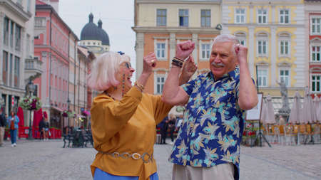 Elderly stylish couple tourists man woman celebrate success win scream rejoices doing winner hands gesture say Yes. Senior travelers grandmother, grandfather enjoying time together. Summer vacation 版權商用圖片