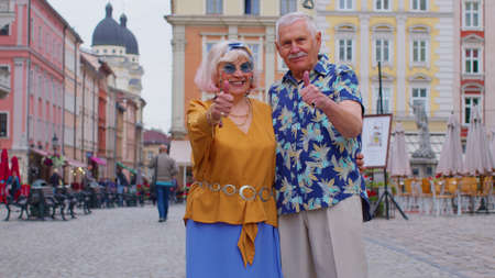 Senior grandmother grandfather tourists raises thumbs up agrees with something or gives positive reply recommends advertisement likes good. Elderly family man, woman on holidays vacation traveling 版權商用圖片