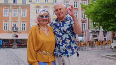 Elderly stylish couple tourists man and woman looking approvingly at camera showing ok gesture, like sign positive something good. Senior travelers grandmother, grandfather on summer vacation trip 版權商用圖片
