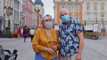 Senior couple tourists grandmother and grandfather in stylish fashion clothing wearing medical protective mask on city street.