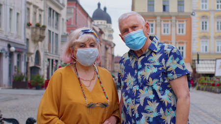 Elderly couple tourists grandmother and grandfather in stylish fashion clothing wearing medical protective mask on city street. 版權商用圖片