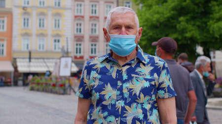 portrait of senior stylish tourist man grandfather wearing protective mask on city street crowd people.