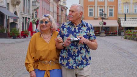 Elderly old stylish tourists man and woman having a walk and talking in city Lviv, Ukraine. Senior grandmother, grandfather with photo camera enjoying conversation, traveling together. Mature family 版權商用圖片