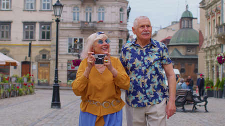 Senior stylish couple tourists man and woman taking photos with old film camera, walking along city street. Elderly travelers grandmother, grandfather enjoying time together. Summer vacation trip