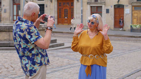 Front view of senior couple man and woman tourists. Elderly grandfather taking photo pictures of grandmother on retro camera. Family enjoying vacations time together in summer old town Lviv, Ukraine