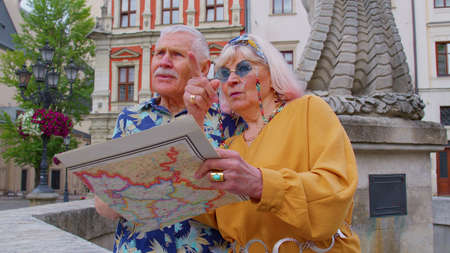 Senior couple grandmother and grandfather tourists in stylish clothing looking for a place to go in new city Lviv, Ukraine, using paper map. Elderly family man, woman on holidays vacation traveling