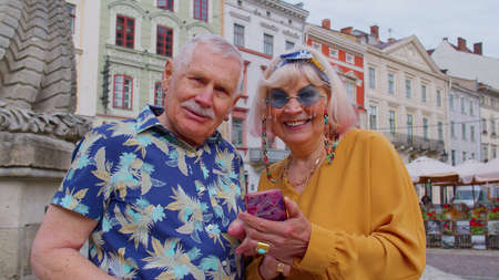 Elderly stylish tourists man woman looking for way using smartphone in old town Lviv, Ukraine. Senior travelers grandmother, grandfather getting lost in big city trying to find route. Summer vacation