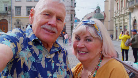 Couple of senior tourists taking selfie in summer city center smiling, looking at camera. POV shot. Elderly grandmother, grandfather enjoying conversation video call, blog vlog. Tourism and pensioners