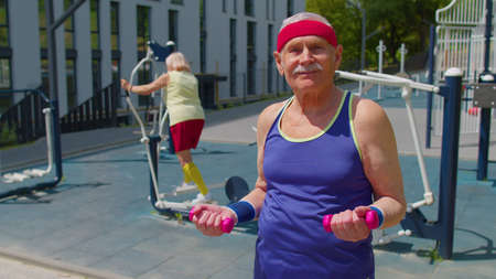 Active senior handsome man grandfather doing sport training weightlifting exercising with dumbbells outdoors on basketball playground. Healthy grandmother doing fitness aerobics routine in background 版權商用圖片