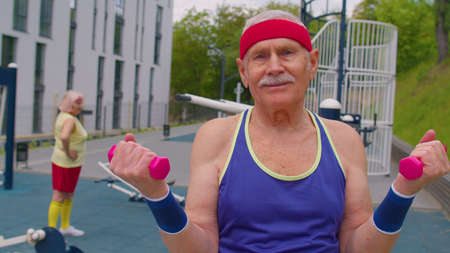 Senior man grandfather doing training weightlifting exercising with dumbbells on basketball playground in park. Sport motivation concept. Active old pensioners family fitness cardio aerobics routine 版權商用圖片