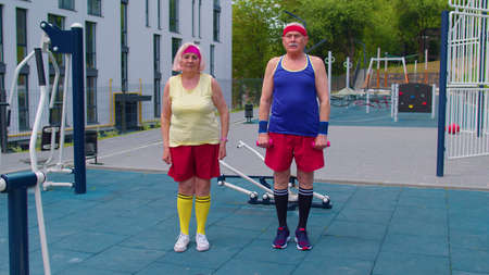 Active senior handsome man and woman doing active training stretching muscles cardio fitness exercising outdoors on basketball playground.