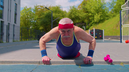 Senior man grandfather 80 years old doing sport training push-ups exercising on basketball playground. Active elderly old pensioner cardio morning aerobics routine. Fitness leisure. Healthy lifestyle 版權商用圖片