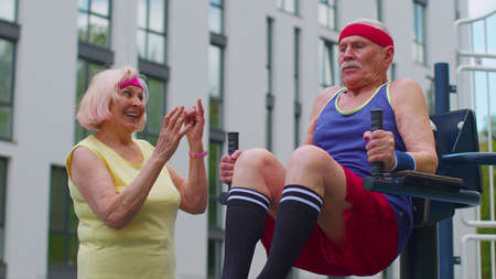 Senior man grandfather doing training abs workout exercising on playground. Sport motivation concept. Active old pensioners fitness cardio aerobics routine. Grandmother coach counting number of times