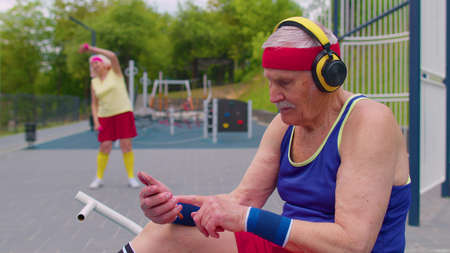 Active senior man grandfather after sport training fitness aerobics cardio exercises listening music from mobile phone wearing headphones on playground. Healthy grandmother working out on background