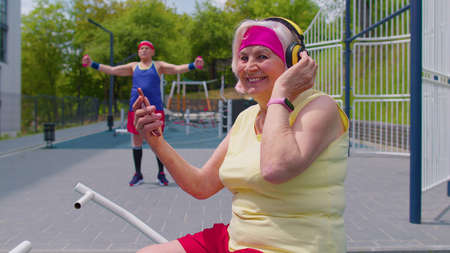 Senior active woman grandmother after sport training fitness aerobics cardio exercises listening music from mobile phone wearing headphones on playground. Healthy grandfather working out on background