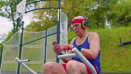 Senior old pensioner grandfather listening music from mobile phone wearing headphones on playground and dancing. Elderly man relaxing after sport training fitness aerobics cardio working out exercises 版權商用圖片