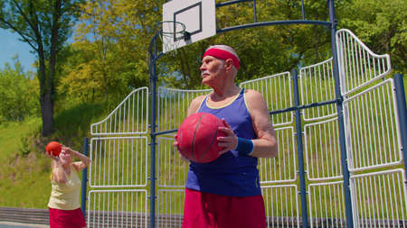 Active senior man grandfather 80 years old posing with ball, looking at camera outdoors on playground court. Healthy grandmother playing basketball in background. Sport motivation for elderly people 版權商用圖片
