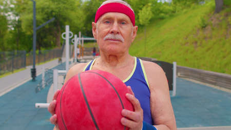 Senior sportsman grandfather athlete posing playing with ball outdoors. Man looking at camera on basketball playground court. Sport motivation for elderly people. Healthy lifestyle. Fitness leisure 版權商用圖片