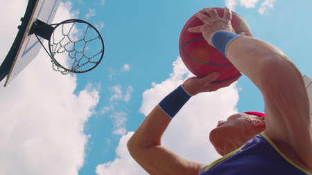Upward view of focused senior player man playing basketball game, successfully hits goal. Active sportsman grandfather trains throwing ball into basket ring on sport playground yard 版權商用圖片