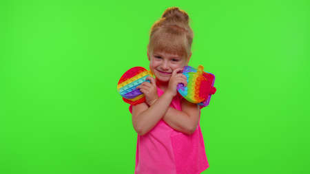 Stylish child girl holding many colorful squishy silicone bubbles sensory toys. Kid playing  popular educational children game showing Ok gesture. Advertising. Chroma key. Stress relief