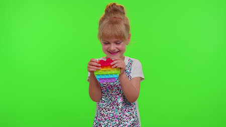 Cute girl playing with pop it sensory anti-stress toy. Chroma key. Child kid presses on colorful rainbow squishy bubbles. Stress anxiety relief. Trendy fidgeting game for stressed children and adults
