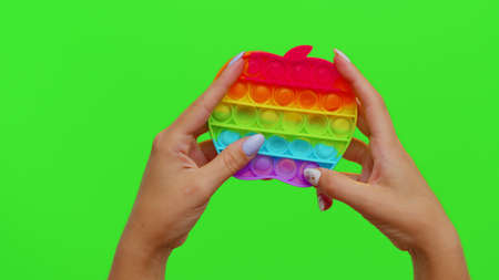 Hands playing with pop up sensory anti-stress toy isolated on chroma key. Girl presses on colorful rainbow bubbles squish. Stress anxiety relief. Trendy fidgeting game for stressed children and adults 版權商用圖片