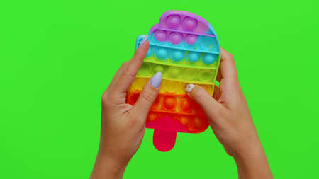 Hands holding colorful squishy silicone bubbles sensory toy isolated on chroma key background. Playing push pop up popular educational children game. Trend 2021. Advertising, copy-space. Stress relief