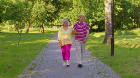 Happy old family husband, wife enjoying time together after retirement. Senior stylish couple grandmother grandfather walking and talking in summer park. Active elderly man pensioner walks with woman