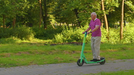 Handsome senior man grandfather tourist riding electric scooter in park. Modern stylish grandpa, new generation. Healthy active cheerful elderly retired guy. Concept of Age Inclusivity and ecological 版權商用圖片