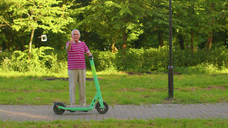 Senior old stylish man grandfather riding electric scooter in summer park. Modern grandpa driving urban vehicle. Healthy elderly retired pensioner guy showing thumbs up. Active life after retirement 版權商用圖片