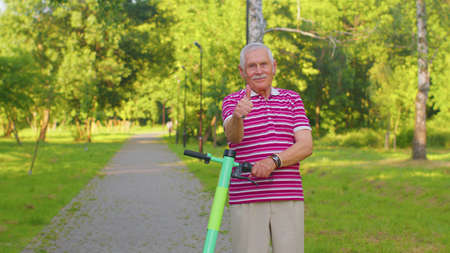 Caucasian old gray-haired senior man grandfather riding electric scooter in summer park. Active modern grandpa driving urban vehicle. Elderly male retired stylish pensioner guy showing thumbs up