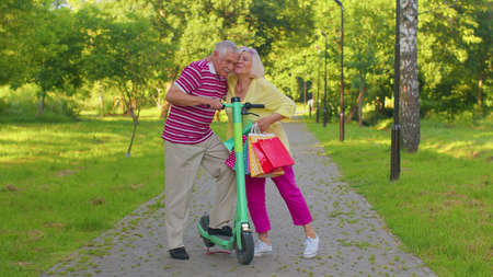 Senior stylish couple tourists man woman walking in summer park with colorful bags after shopping and using electric scooter for riding. Elderly grandmother, grandfather enjoying weekend time together